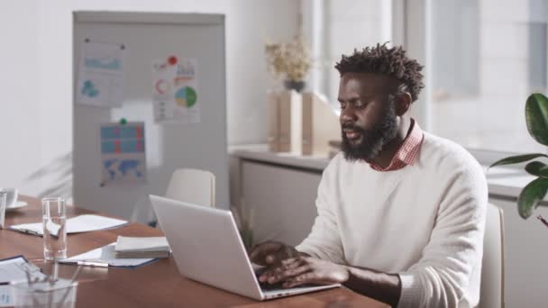 Medium portrait of modern African American businessman wearing casual outfit sitting at table in office room working on laptop
