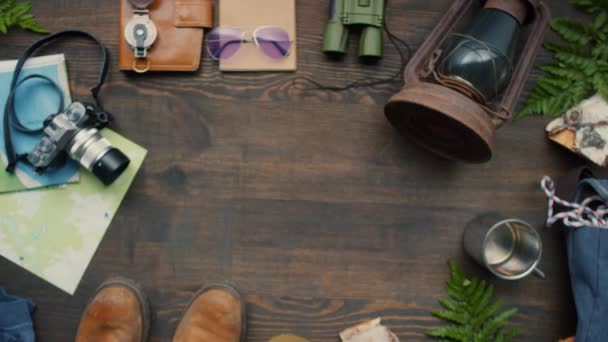 Top view flat lay shot of unrecognizable woman putting two passports on wooden table with travel accessories lying on it