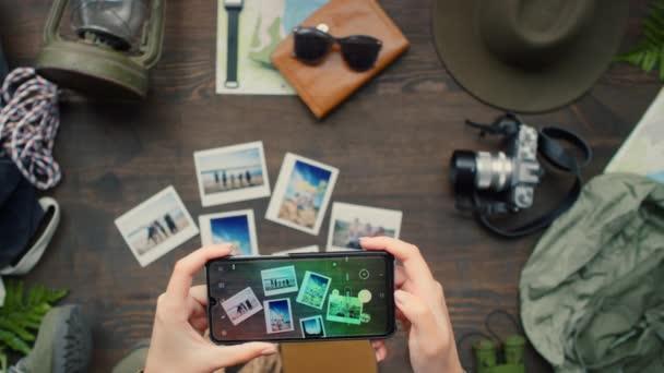 Horní pohled záběr nerozpoznatelné ženy držící mobilní telefon a fotící fotografie a cestovní doplňky ležící na dřevěném stole