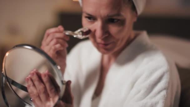 Nahaufnahme einer attraktiven lächelnden Frau, die in den Spiegel schaut, während sie Eiswürfel auf die Haut reibt und nach dem Bad Schönheitsübungen macht