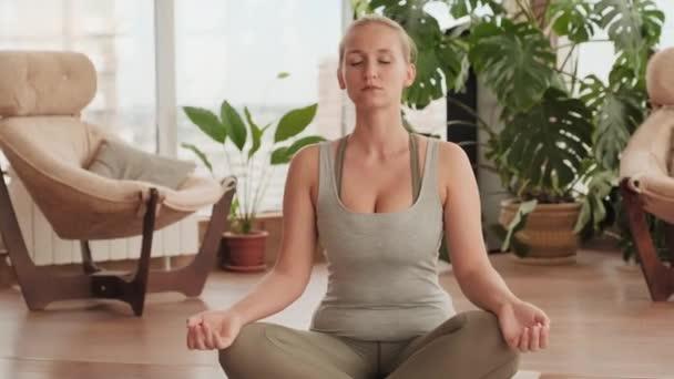 Mittlere Aufnahme einer jungen attraktiven Frau, die in Lotus-Pose auf einer Yogamatte sitzt und mit geschlossenen Augen in einem hellen, geräumigen Studio meditiert