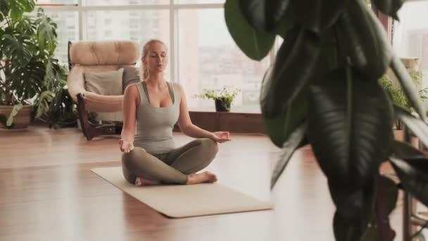 Vollbild einer Frau mit geschlossenen Augen, die auf einer Yogakarte auf dem Boden im hellen Fitnessstudio sitzt und allein in Lotusposition meditiert