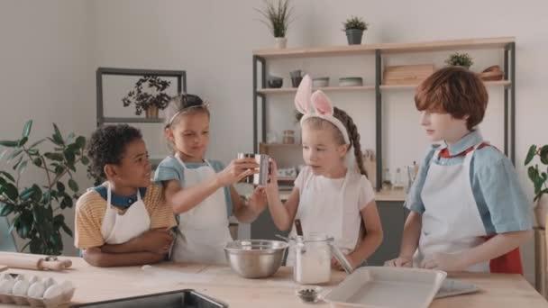 Többnemzetiségű férfi és női iskolai barátok kötényben beszélgetnek, mosolyognak, főznek, asztalnál állnak a konyhában. Nyuszifül-fejpántos lány lisztet önt a szitán keresztül, a gyerekek játszanak vele.