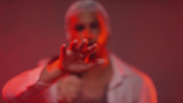 Arckép egy jóképű, fehér hajú férfiról, csillámporos sminkkel és virágos inggel a meztelen mellkasán, ahogy a kamerába néz és pózol.