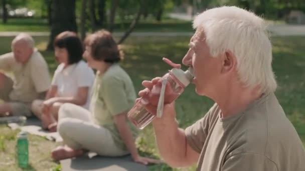 Mittlere Aufnahme eines betagten kaukasischen Mannes, der Wasser aus einer Sportflasche trinkt, während im Hintergrund drei ältere Menschen auf Matten im Gras im Park sitzen