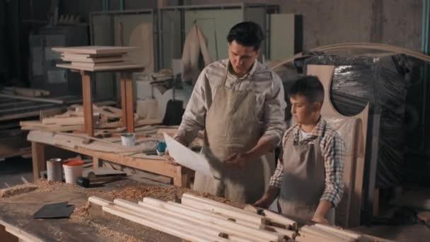 Mittlere Aufnahme von Vater und Sohn, die gemeinsam Zeit in einer Tischlerei verbringen und den Entwurf von Möbeln aus Holz betrachten
