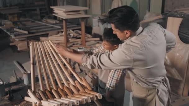 Mittlere Zeitlupe zeigt männliche Arbeiter in Vintage-Hemden und Schürzen, die Pinsel in der Hand halten und Holzplanken von handgefertigten Liegestühlen in der Tischlerei polieren