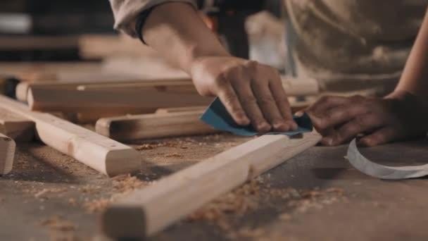 Detailní záběr nerozpoznatelného řemeslníka broušení kus dřeva s pískovým papírem odfoukávání pilin ze stolu pracuje v truhlářství