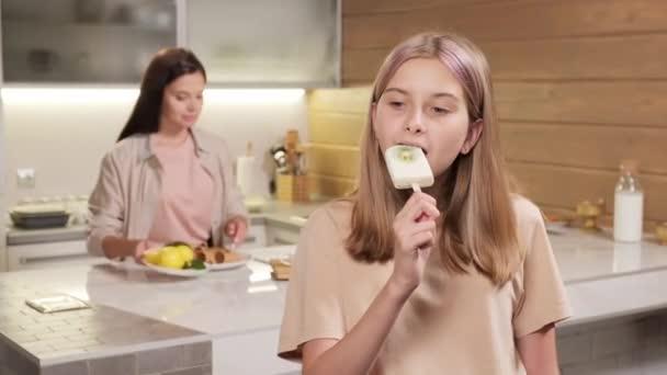 Pas-up portrét hezké mladé dívky jíst domácí zmrzlinu na hůl s úsměvem na kameru, zatímco její matka slouží vaření stůl v pozadí v jasné kuchyni
