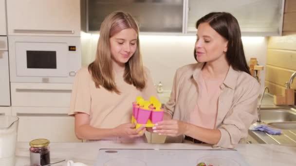 Közepes adag vidám fiatal nő időt tölt a lányával házi készítésű jégkrémet főzve együtt mosolyogva és beszélgetve a fényképezőgéphez, ami műanyag formákat mutat a jégkrémhez.