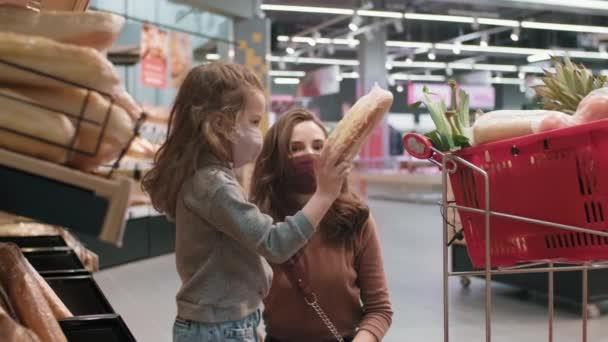 Střední zpomalený záběr mladé matky a dcery v ochranných maskách při každodenním nakupování potravin ve velkém supermarketu při výběru čerstvého chleba při jeho umístění do nákupního košíku