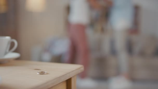 Egyszemélyes jegygyűrű a konyhaasztalnál szelektív fókuszban és boldogtalan, stresszes pár vitatkozik a nappaliban homályos háttérrel