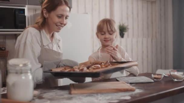 Pas-up záběr šťastné mladé bělošky žena přináší horké preclíky na pečení prostěradla a holčička tleskání vonící lahodné pečené jídlo