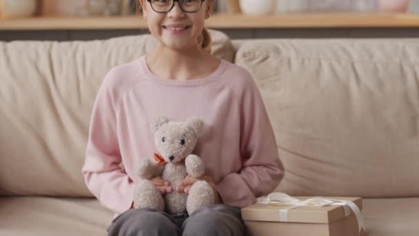 Aufklappbares Porträt des hübschen kleinen Mädchens mit Brille und bunter Festmütze, das auf dem Sofa im Wohnzimmer sitzt und den weißen Stoffhasen aus der Geschenkbox umarmt, der in die Kamera lächelt