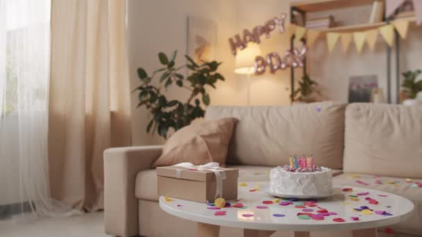 No people panning shot of cozy living room decorated with birthday balloons and confetti, birthday cake with burning candles and craft gift box