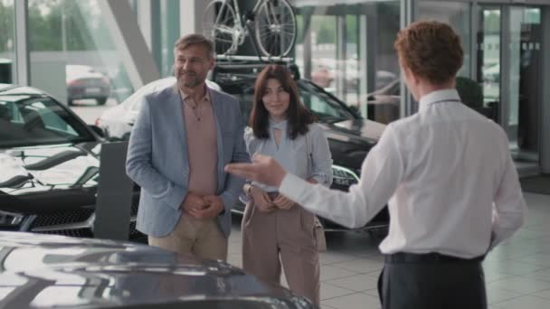 Slowmo of young salesman in formal attire standing by expensive car in dealership and talking to cheerful couple