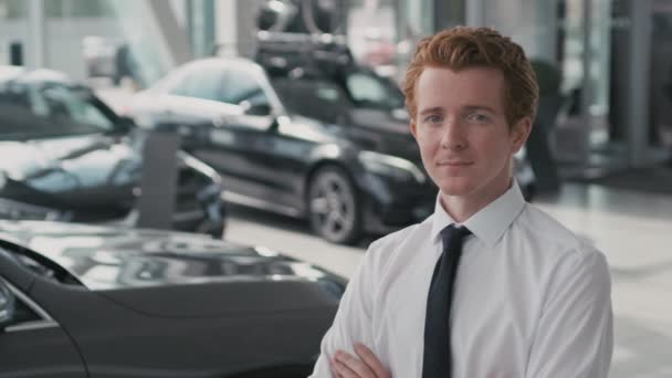 Slowmo portrait of young car salesman in necktie and white shirt standing with his arms crossed and looking at camera in dealership