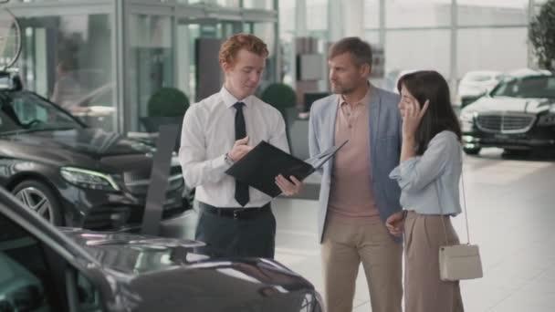 Sledování mladého prodejce prodejců ve formálních šatech držení složky a zobrazování automobilové dokumentace na pár nákupů pro nové vozidlo