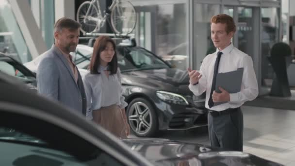 Tracking shot of young car salesman with clipboard talking to couple in dealership, then shaking hand of man