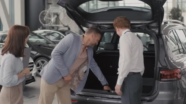 Tracking shot of young salesman in formal attire showing boot of car to cheerful couple in dealership. He is answering their questions and smiling