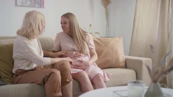 Mittlere Zeitlupe: Junge Schwangere, die in die Wehen geht, spürt, wie Farbe den Bauch berührt, während ihre Mutter den Krankenwagen ruft, der auf dem Sofa im Wohnzimmer sitzt