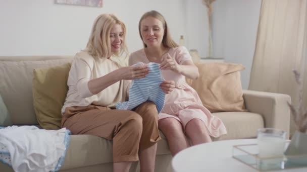 Mittlere Zeitlupe zeigt junge schwangere Frau, die Neugeborenes der glücklichen Mutter zeigt, die zusammen auf dem Sofa im hellen Wohnzimmer sitzt