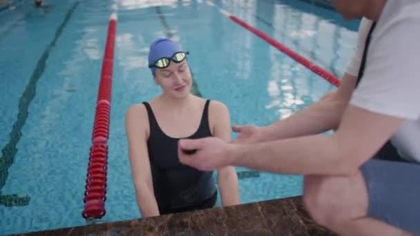 Slowmo sledování veselého ženského plavce stojící v bazénu a usmívající se při poslechu svého mužského trenéra dávat jí rady