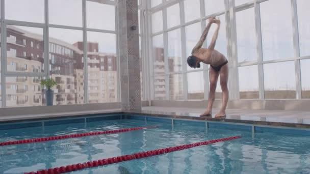 Střední záběr profesionálního muže plavce v brýlích, trenýrkách a čepici zahřívá a natahuje paže a záda před tréninkem