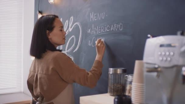 Střední side-view záběry mladého atraktivního asijského kávovaru pracovníka psaní na tabuli názvy kávových nápojů v menu příprava kavárny pro otevření