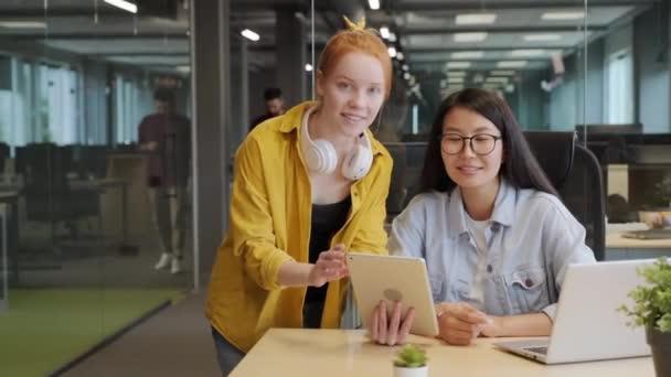 Střední zpomalený portrét dvou multietnických kolegyň diskutujících o projektu na digitálním tabletu, pak se dívajících na fotoaparát s úsměvem