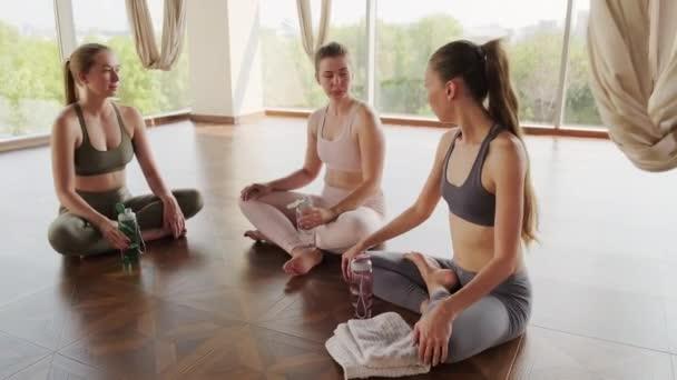 Ruční blázen záběr dívek ve sportovním oblečení sedí v lotosu póza chatování spolu a popíjení vody, odpočívá po tvrdém cvičení jógy