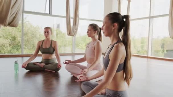 Vollständige Aufnahme von Mädchen, die in Lotuspose auf dem Boden sitzen, meditieren und sich in einem hellen, geräumigen Studio mit Panoramafenstern konzentrieren