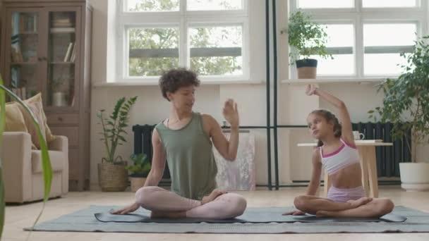 Tracking Shot von fitter junger Mutter und kleiner Tochter in Sportbekleidung, die im Schneidersitz auf einer Yogamatte sitzen und sich zusammen im Wohnzimmer strecken