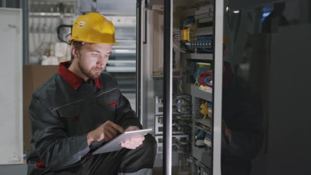 Střední zpomalení detailní záběr mužského elektrikáře v bezpečnostní helmě kontrola elektrického panelu v továrně pomocí digitálního tabletu