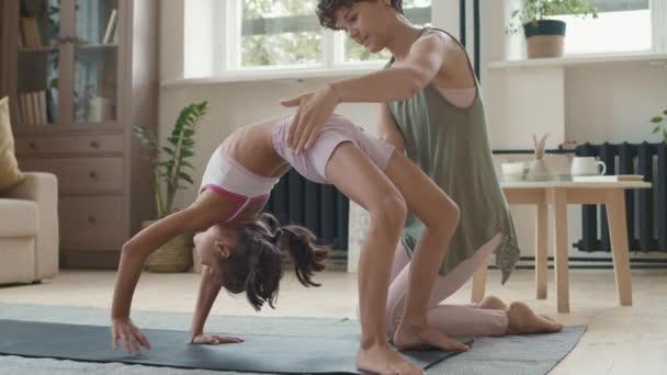 Slowmo sledování záběr mladé matky ve sportovním oblečení pomáhá její dceři dělá nahoru luk pózovat na podložce jógy doma