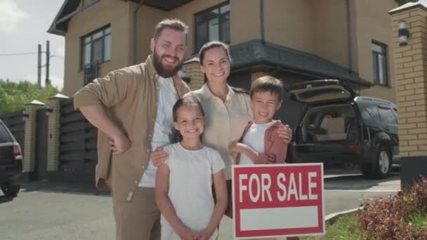 Portrait of happy family of four posing together before suburban house and sign For Sale