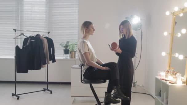 PAN slowmo of female MUA artist applying make-up on face of beautiful female model sitting on chair in studio