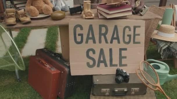 Handabdrücke verschiedener Second-Hand-Waren bei Garagenverkauf im Vorgarten eines Vororthauses