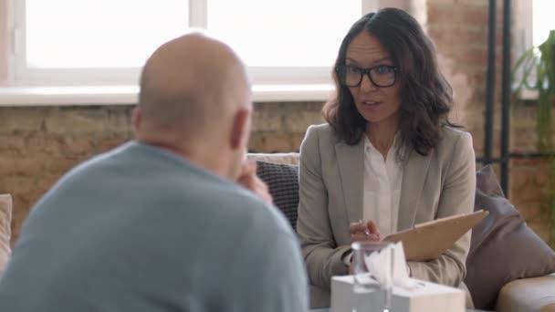Sledování záběru ženské psychoterapeutky v brýlích psaní poznámek do schránky a mluvení s emocionálním klientem během terapie v její soukromé praxi
