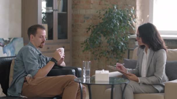 Pomalý střední snímek úzkostlivého mladého muže sedícího na gauči a hovořícího s terapeutkou se schránkou