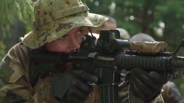 Closeup of brutal spetsnaz officer with squad investigating territory of forest armed with sniper rifles