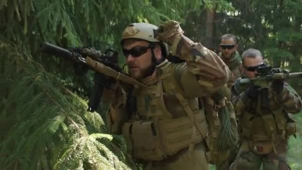 Medium closeup of squad of special forces with rifles on secret operation in jungle, investigating territory