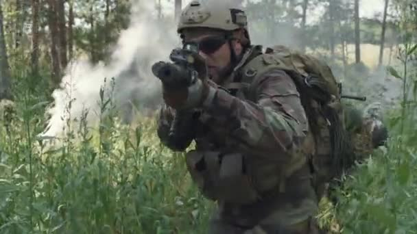 Medium footage of brutal soldiers in camouflage uniform walking towards camera with sniper rifles along smoky battlefield
