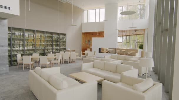Slow-motion no people handheld footage of bright luxurious lobby with beige furniture and glass liquor cabinet