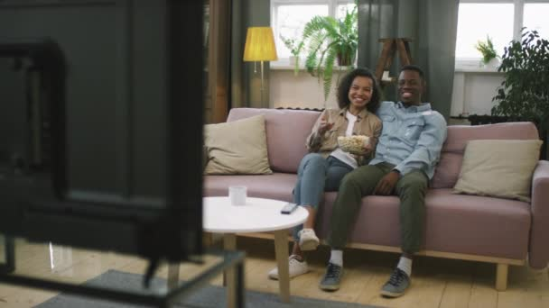 Slow-motion panning full shot of smile young afro couple watching funny sitcom on TV, sitting on gauč in living room eating popcorn, laugh from time to time