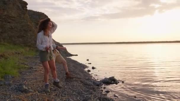 Hravý mladý muž a žena v lásce skákání oblázky přes vodní hladinu jezera na teplý jarní večer