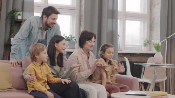 Střední záběr velké radostné rodiny sedící na gauči v obývacím pokoji s video konverzace s přáteli smích a pozdrav