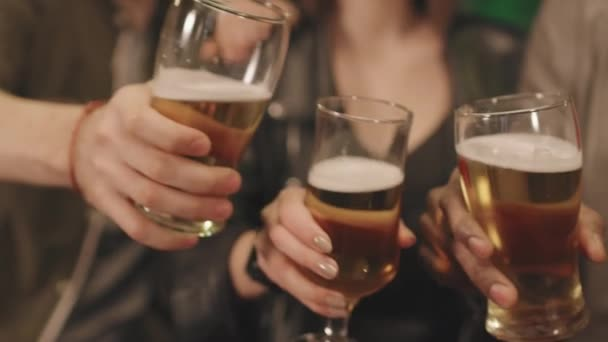 Slow-motion closeup of unrecognizable people toasting glasses of beer on camera chilling at bar