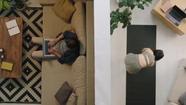 Top view of life of people separated by wall in apartment building. Man sitting on couch and working on laptop as young woman doing fitness on yoga mat
