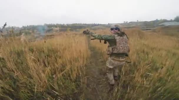 Point-of-view footage of group of professional special forces soldiers going through field, firing guns to enemies while performing dangerous military operation